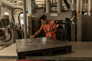 A freshly moulded plastic pallet is inspected at Re Pal Recycling facility. Re Pal handles 10,000 ...