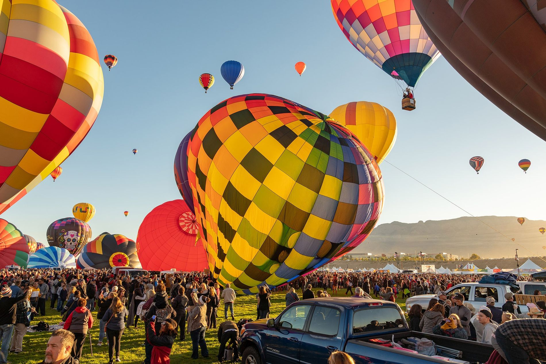 Pilots prepare their balloons to ascend shortly after dawn at the Albuquerque International Balloon Fiesta.