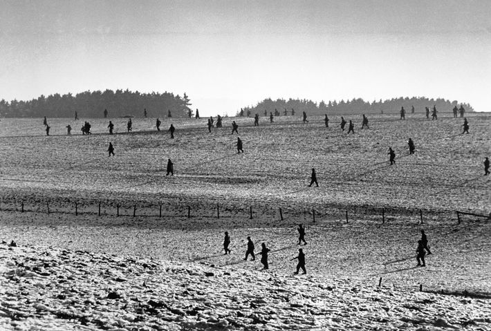 Recovering from the December 16 attack, U.S. soldiers advance across a field near Bastogne, Belgium, shortly ...