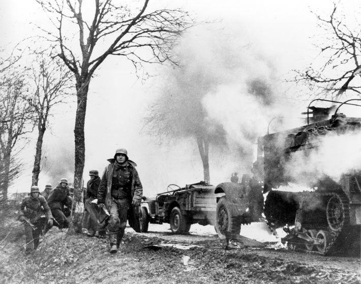 German infantrymen pass burning American vehicles during the Battle of the Bulge. Reich convoys were often ...