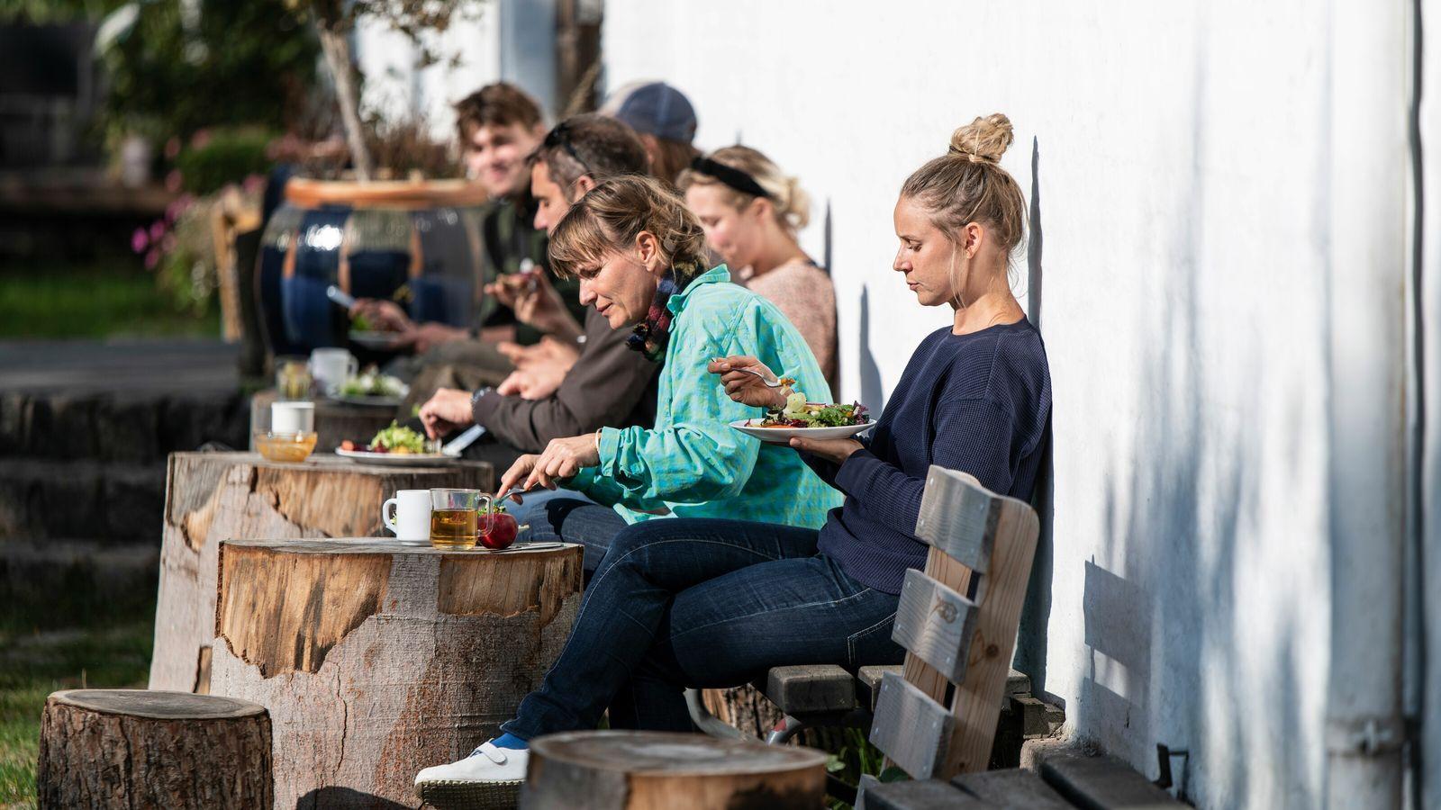 Residents of Svanholm, Denmark's largest commune, sharing lunch in the sunshine.