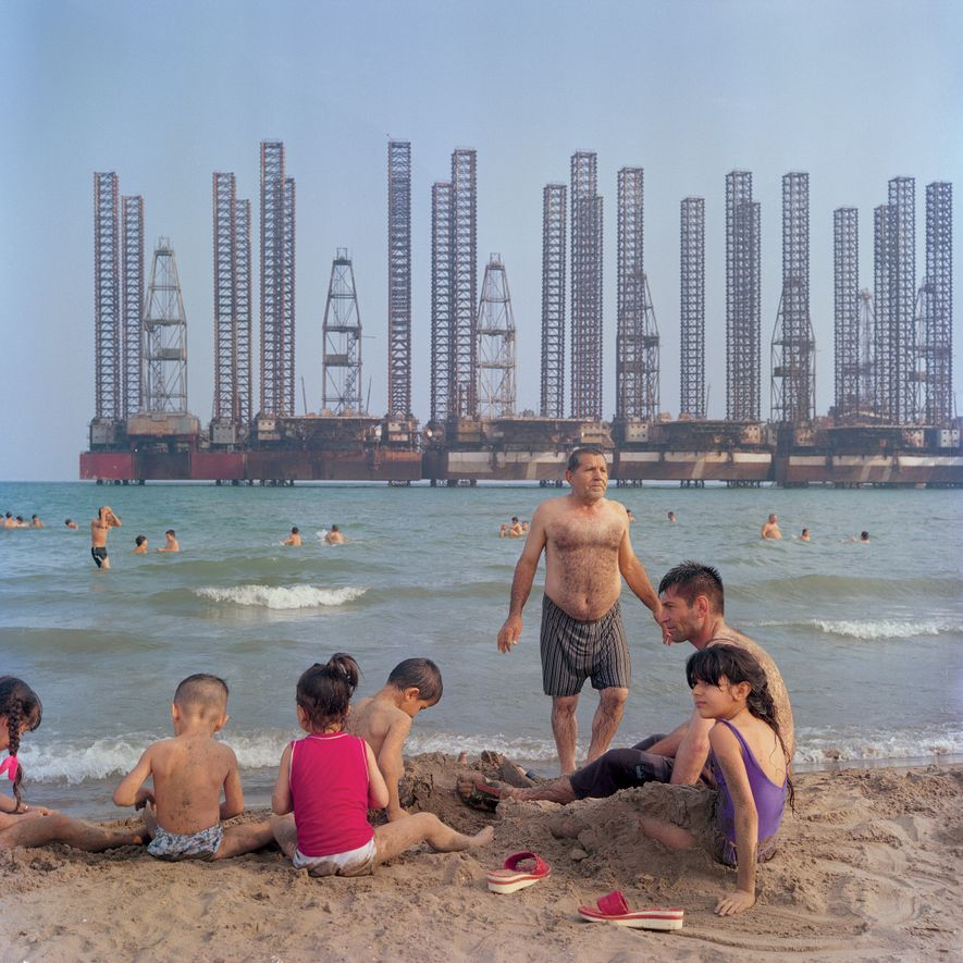 A family enjoys downtime with idle Soviet oil rigs at Shikhov beach, 10 miles south of Baku.
