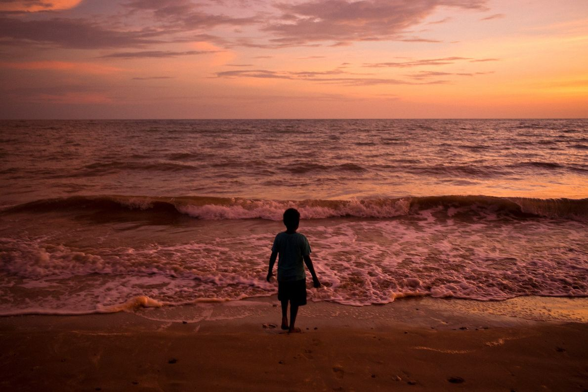 The sun sets over Melville Island, casting the water in vibrant shades of pink and orange.