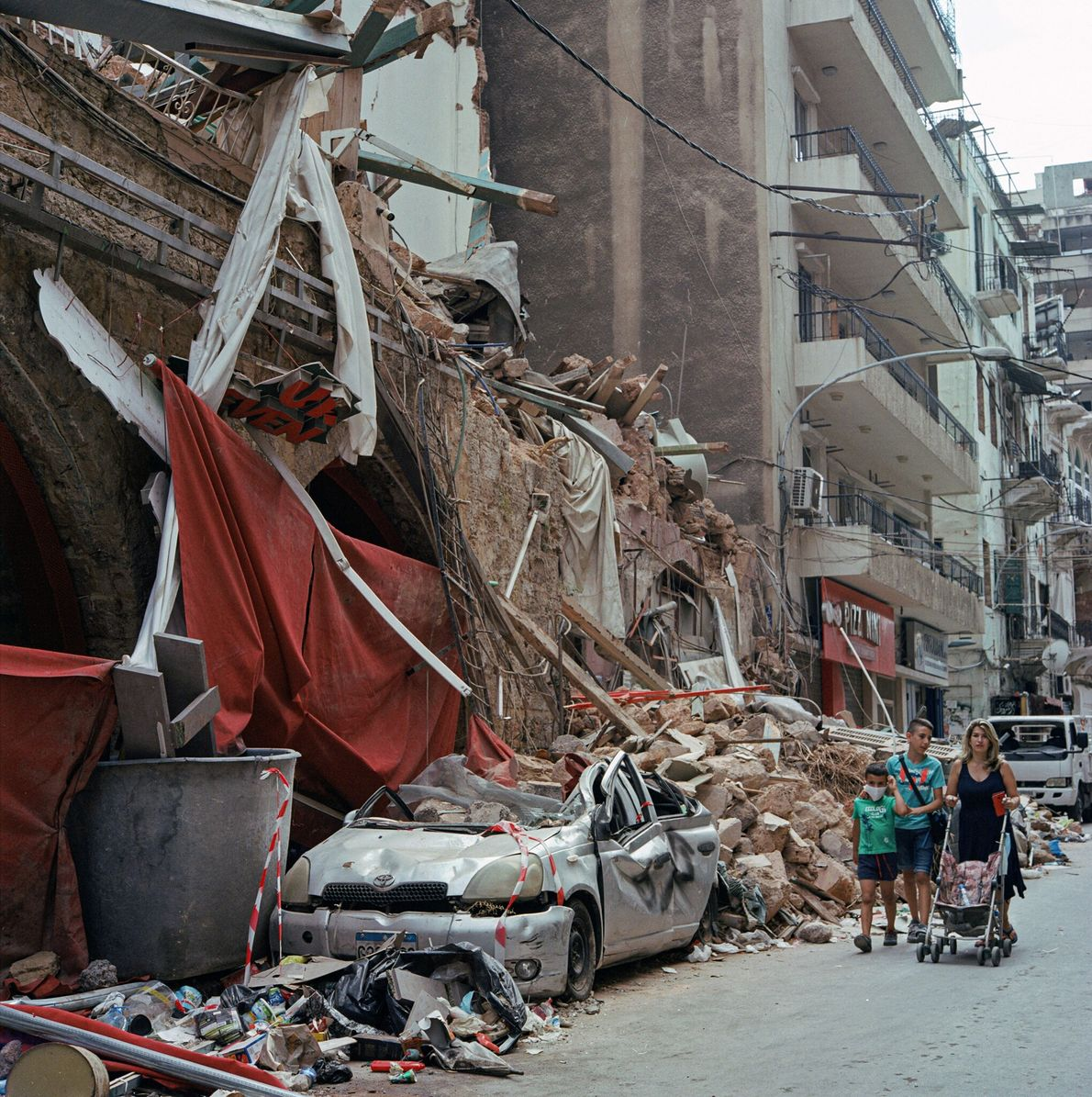 Pedestrians walk past a crumbled building in the Mar Mikhael neighborhood of Beirut, Lebanon after a ...
