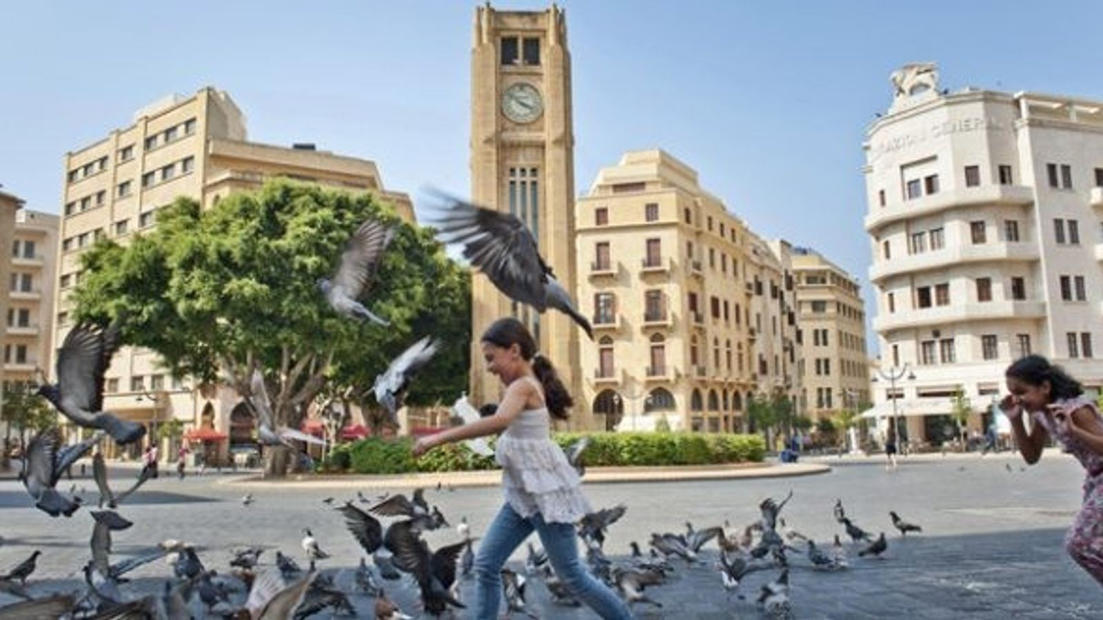 Girl chases pigeons in a square, Beirut