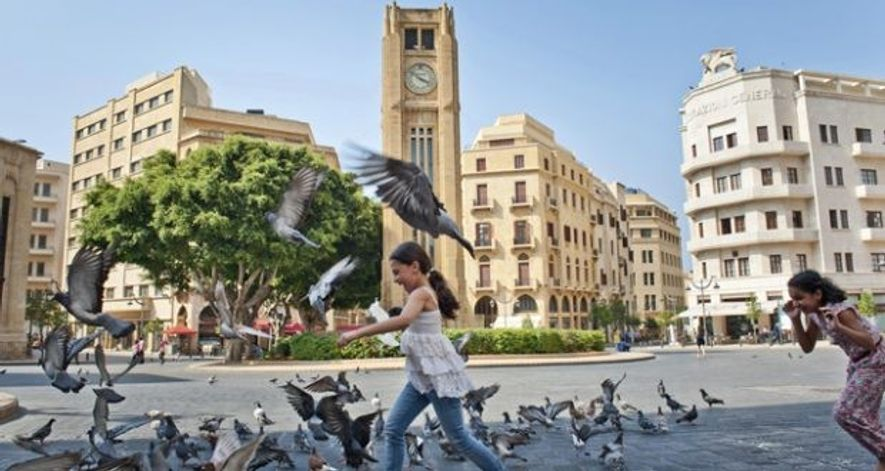 Girl chases pigeons in a square, Beirut.