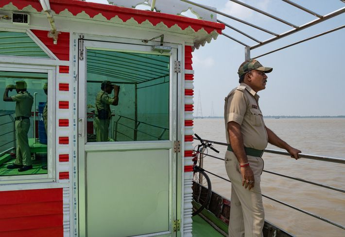 A West Bengal police boat patrols the Hooghly River in the Sundarbans, a watery area with ...