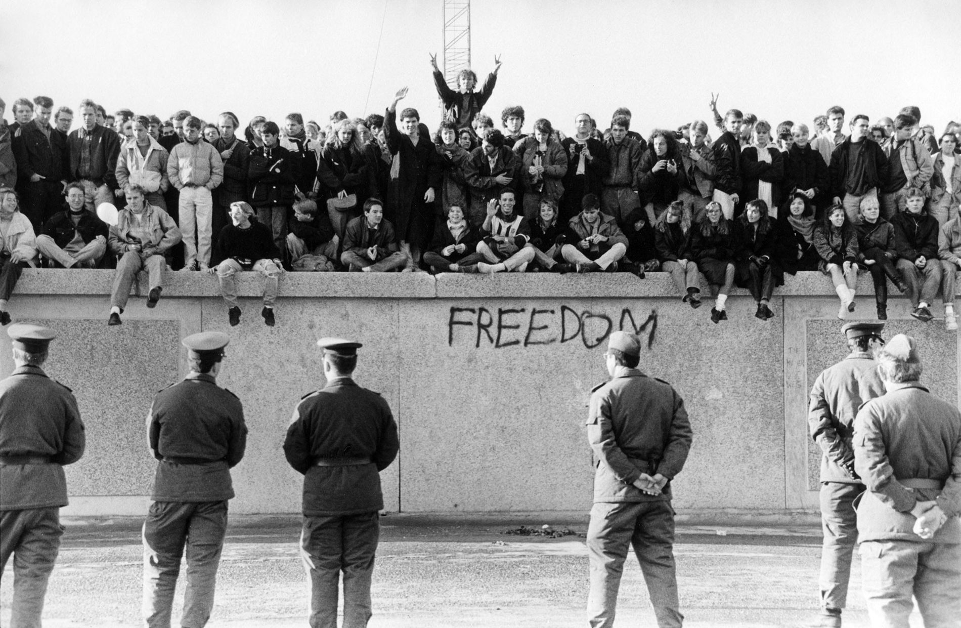 West Germans scale the Berlin Wall before East German guards as the Cold War barrier came ...
