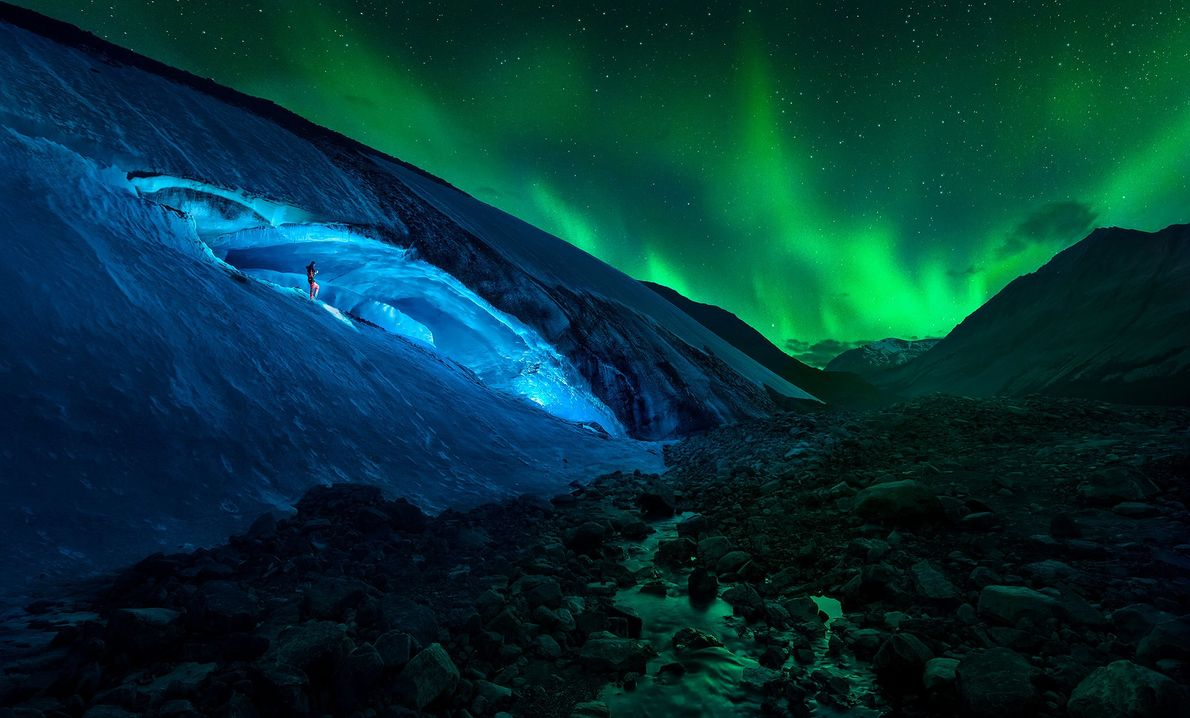 A hiker treks down an icy slope outside an ice cave on the Athabasca Glacier inside ...