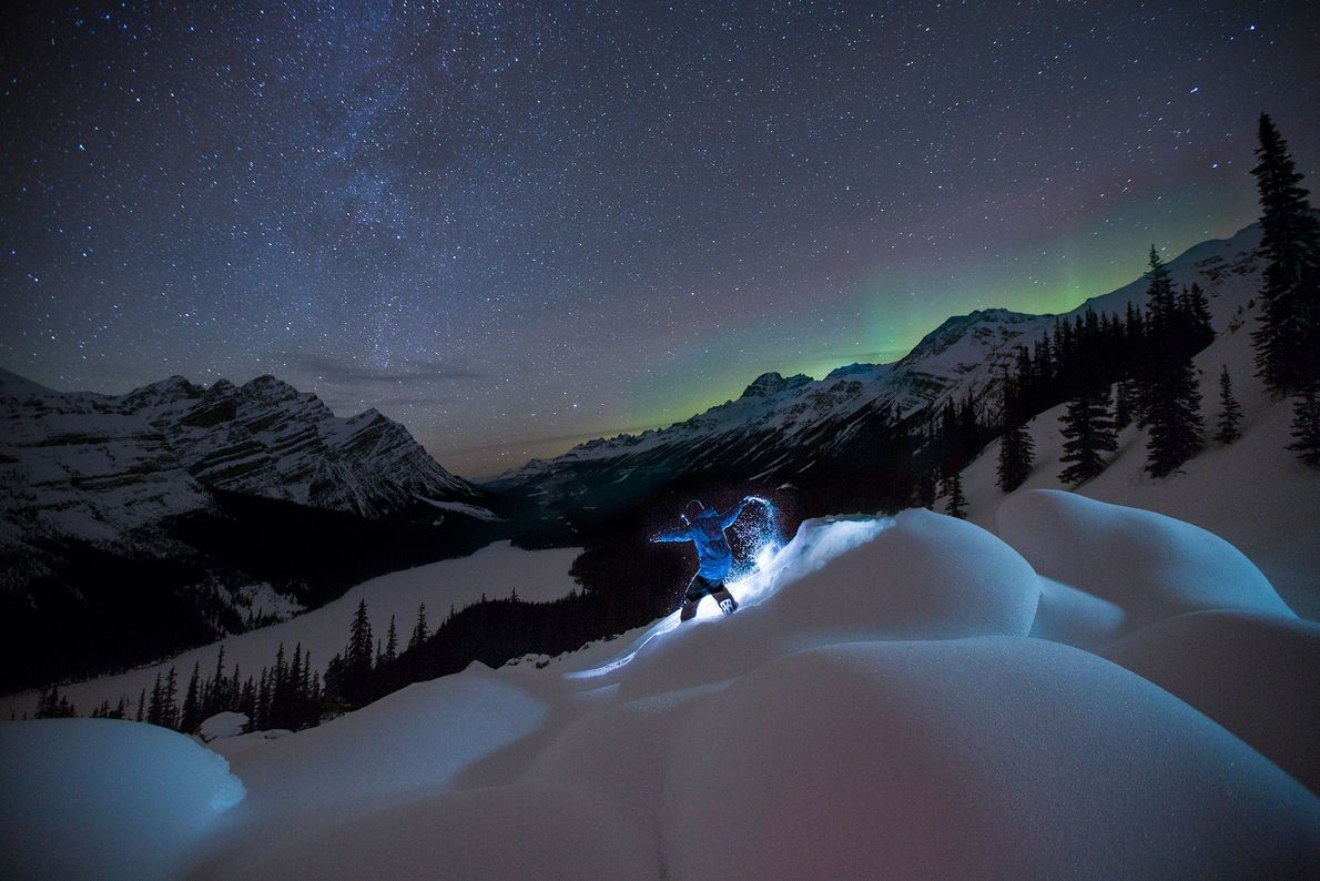 A snowboarder carves through the snow above Canada's Peyto Lake in Banff National Park.