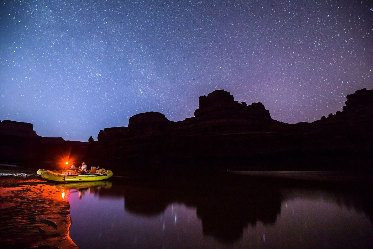 Rafters pause along the Colorado River to see dazzling stars in the night sky.