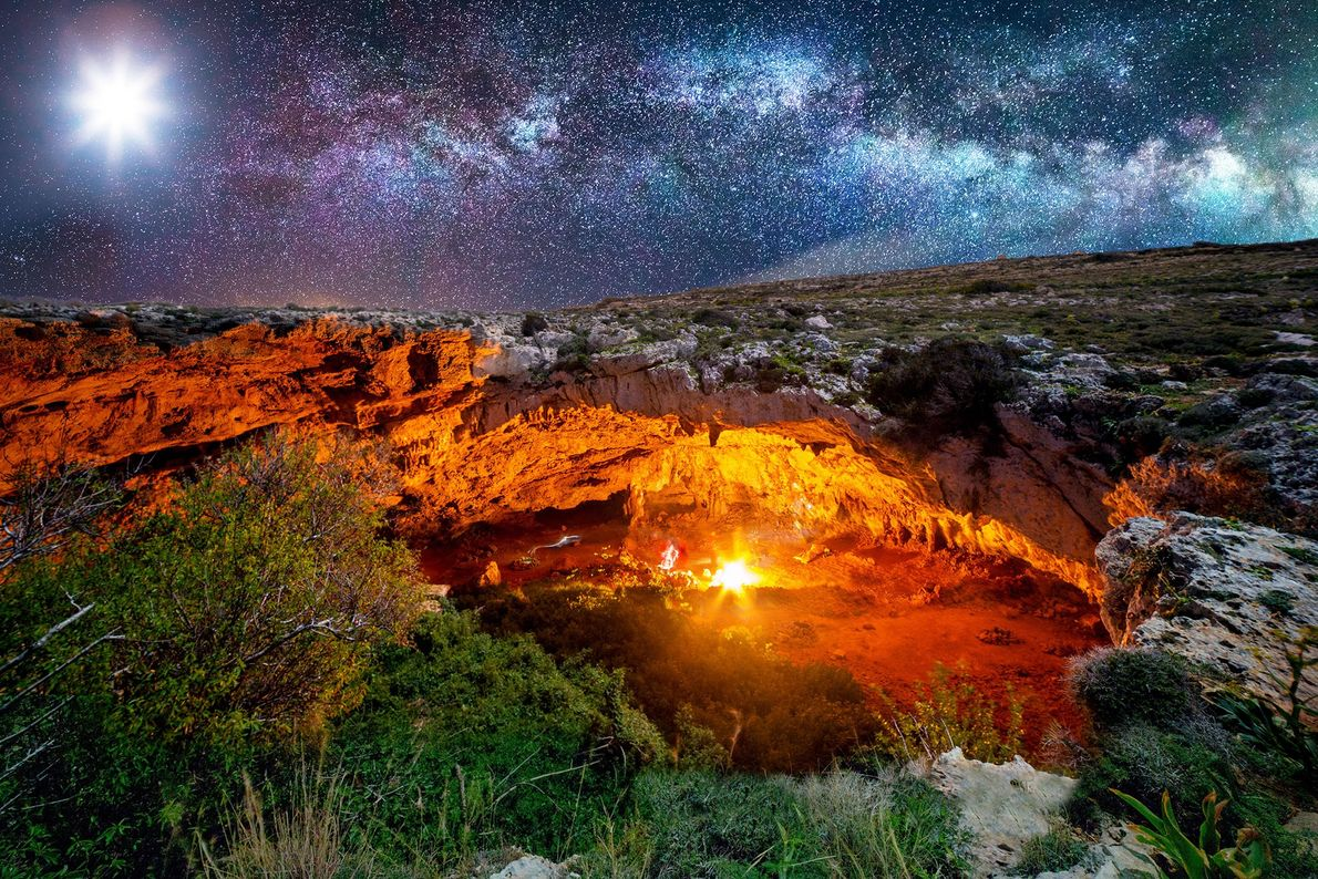 The moon and a roaring campfire light the way for climbers at Malta's Ghajn Tuta Cave.