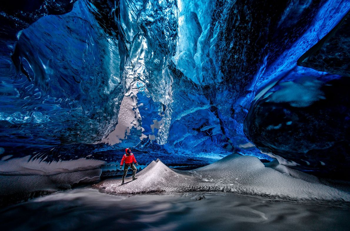 A hiker stands inside a glacial cave in Vatnajökull, Iceland.