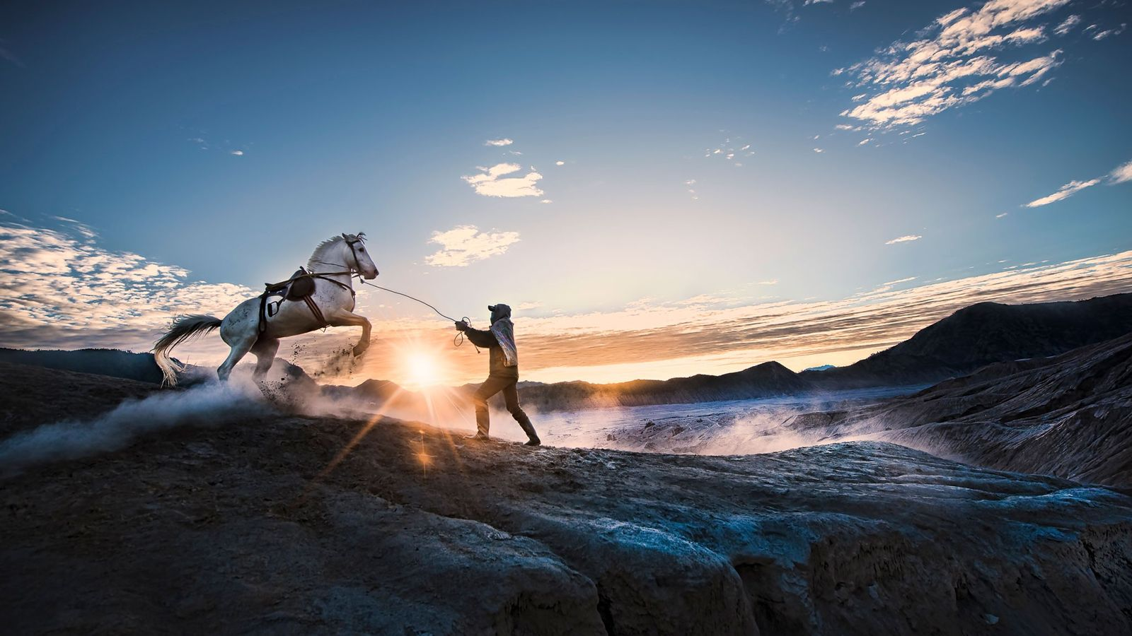 A horse trainer holds the rope of his steed near the crater of Indonesia's Mount Bromo.