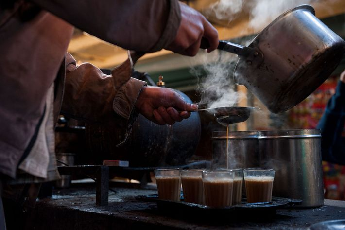 A man pours hot water into a filter to make chai.
