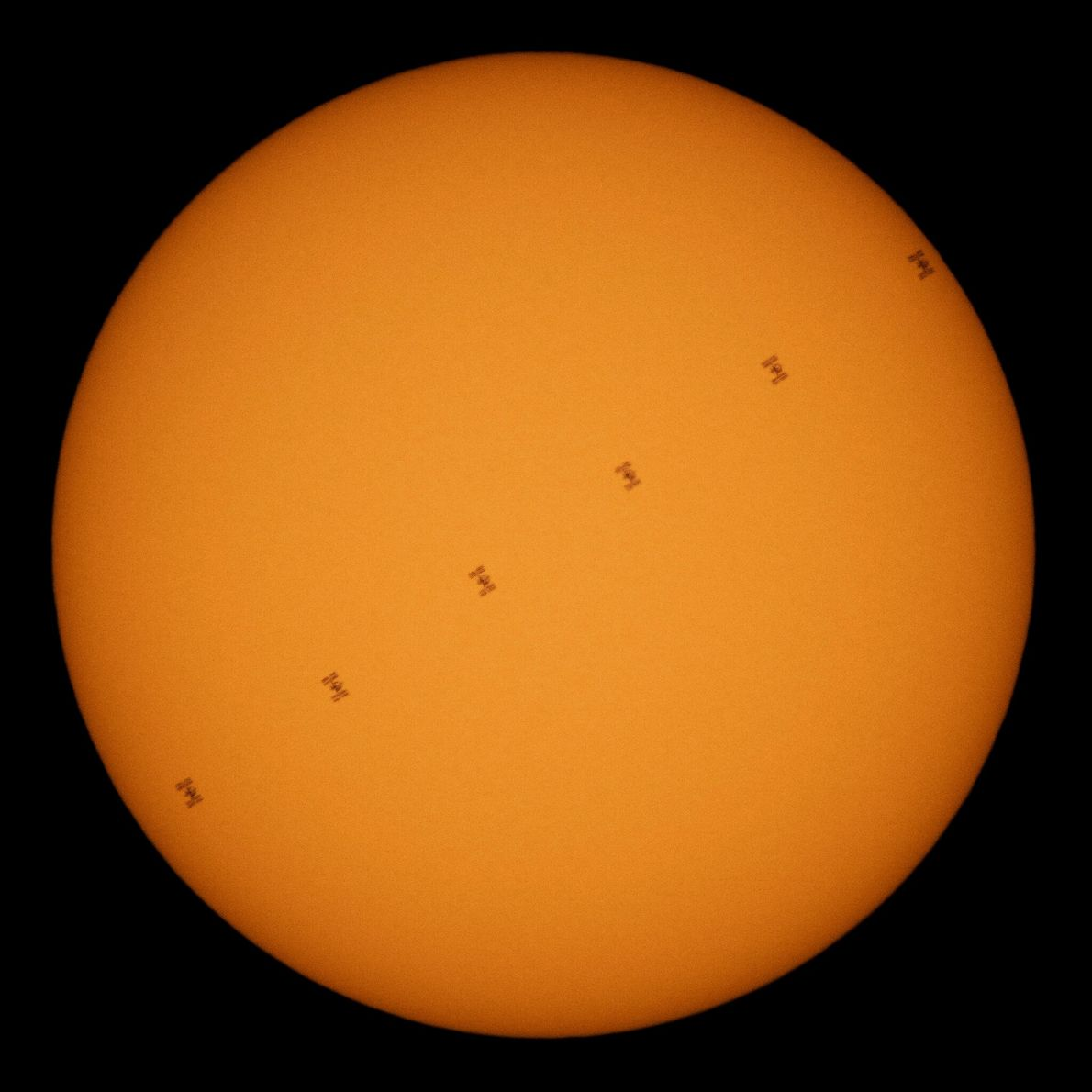 A march of black dots against a glowing disk, the International Space Station transits the sun ...