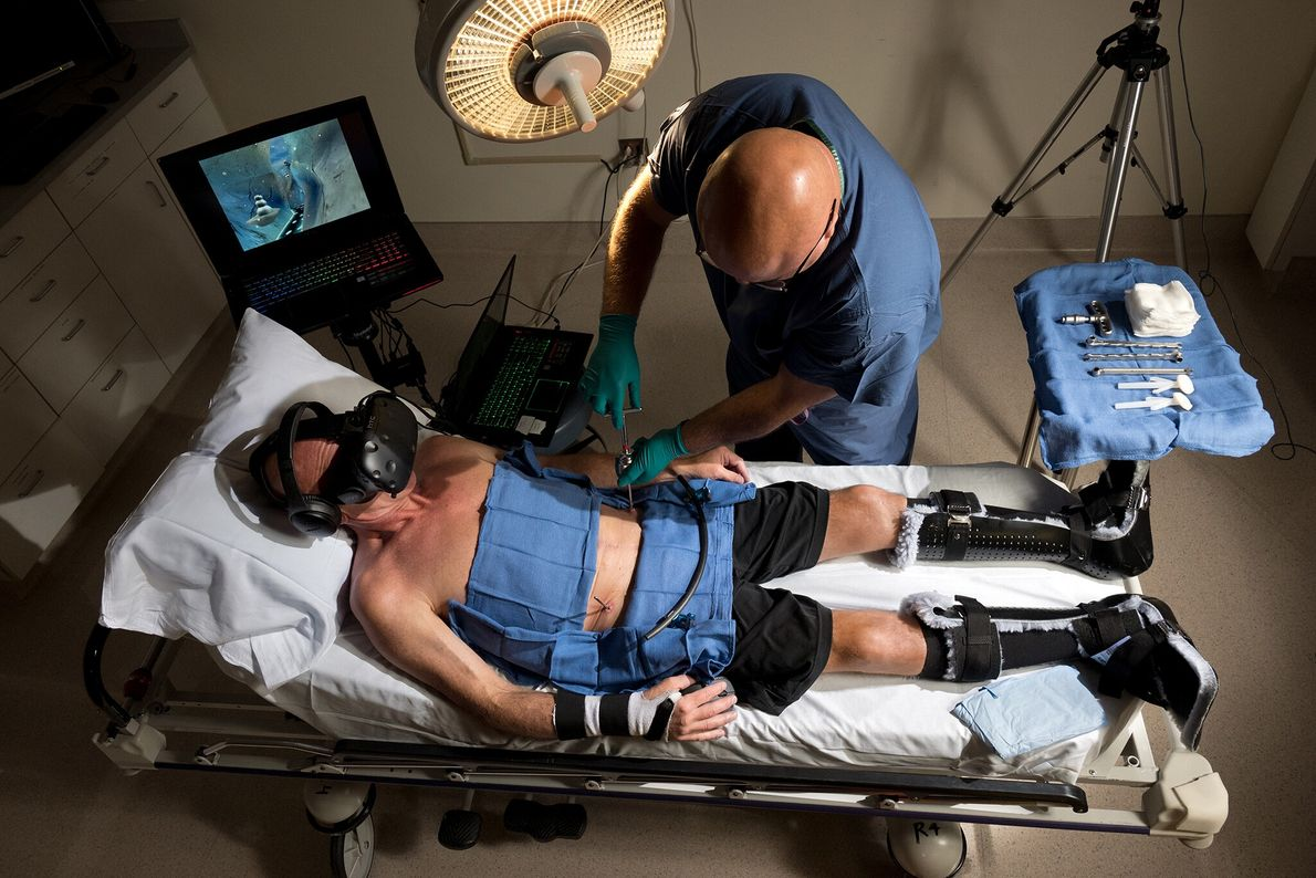 During surgery at UW Medicine's Harborview Medical Center in Seattle, patient Brent Bauer eases his pain ...