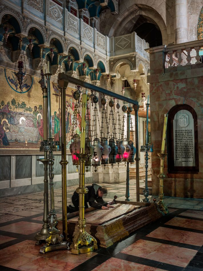 A pilgrim inside the Church of the Holy Sepulchre kneels at the Stone of Unction, which ...