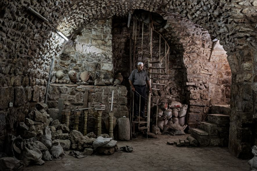 Licensed by the Israeli government to sell antiquities, Khader Baidun visits a storage room below one ...