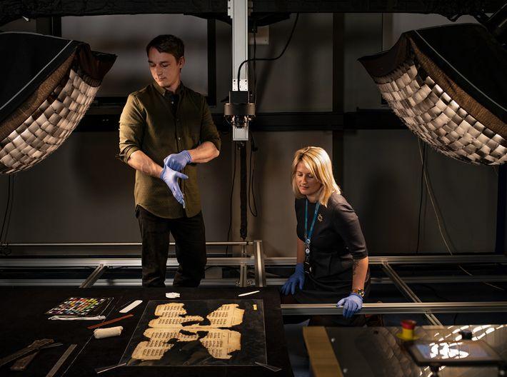 At the Cambridge University Library's Digital Content Unit, technicians Błażej Mikuła and Amélie Deblauwe position pages ...