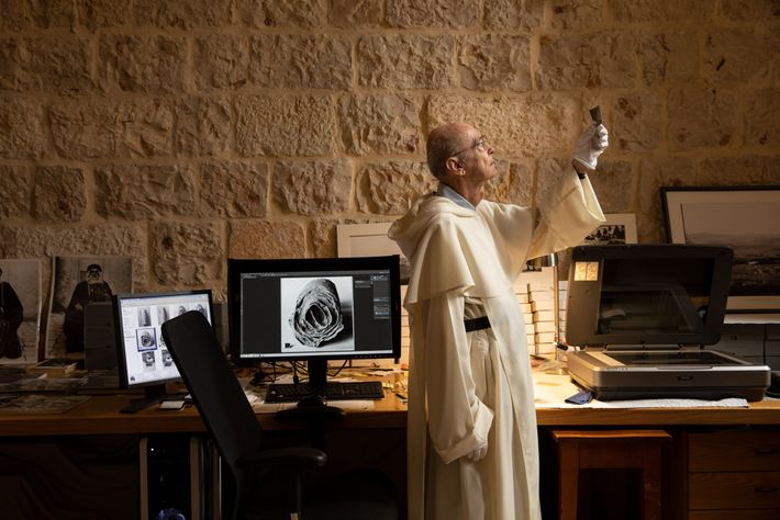 Dominican Father Jean-Michel de Tarragon studies archival photographs at the French École Biblique in Jerusalem. Its ...