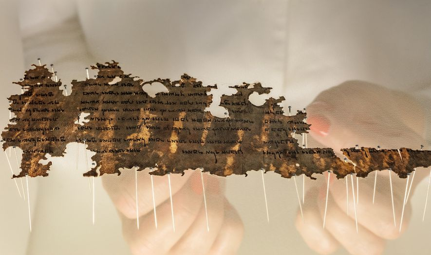A conservator at the Israel Antiquities Authority prepares a fragment of the Dead Sea Scrolls for ...