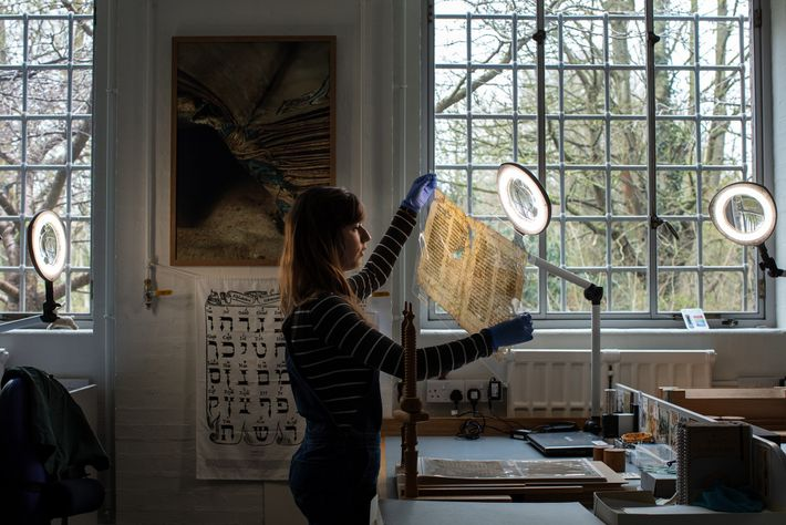 Conservator Emma Nichols examines a Hebrew text at the Cambridge University Library, which houses some 200,000 ...