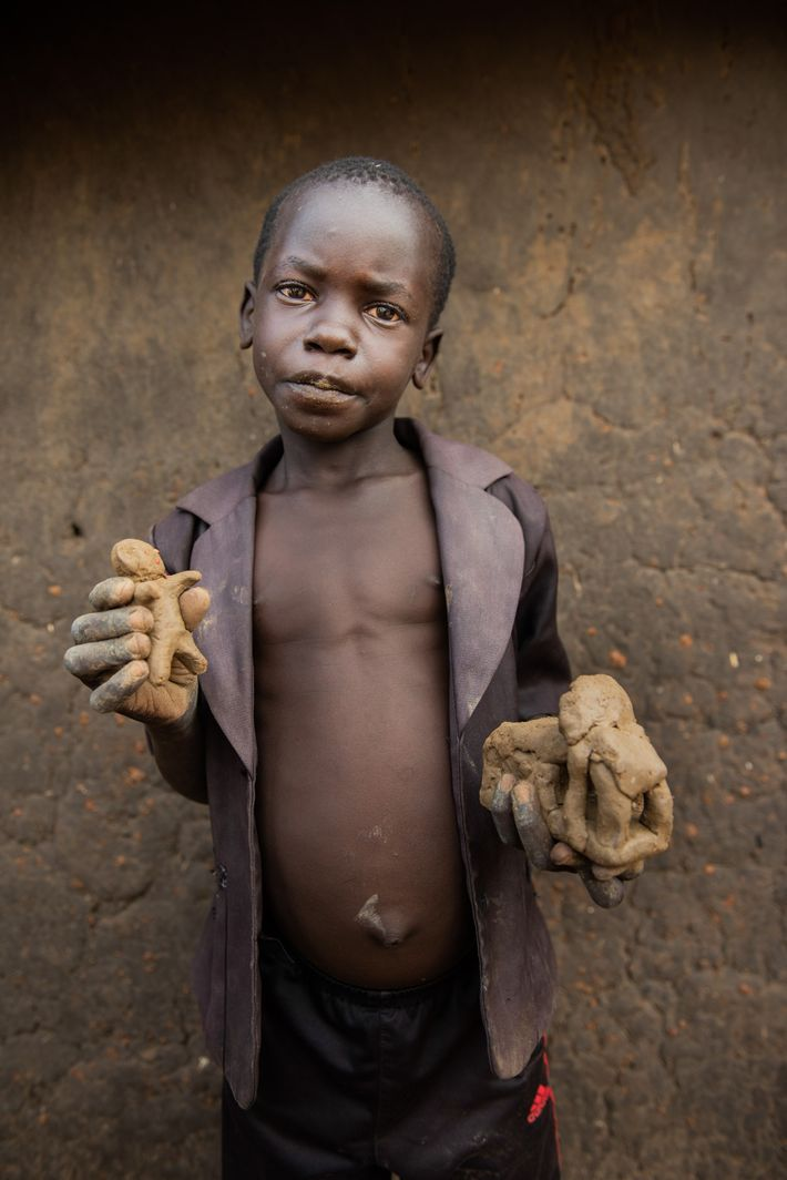 Omar Basir, a Ugandan from one of the villages within Bidibidi, holds a doll and car ...