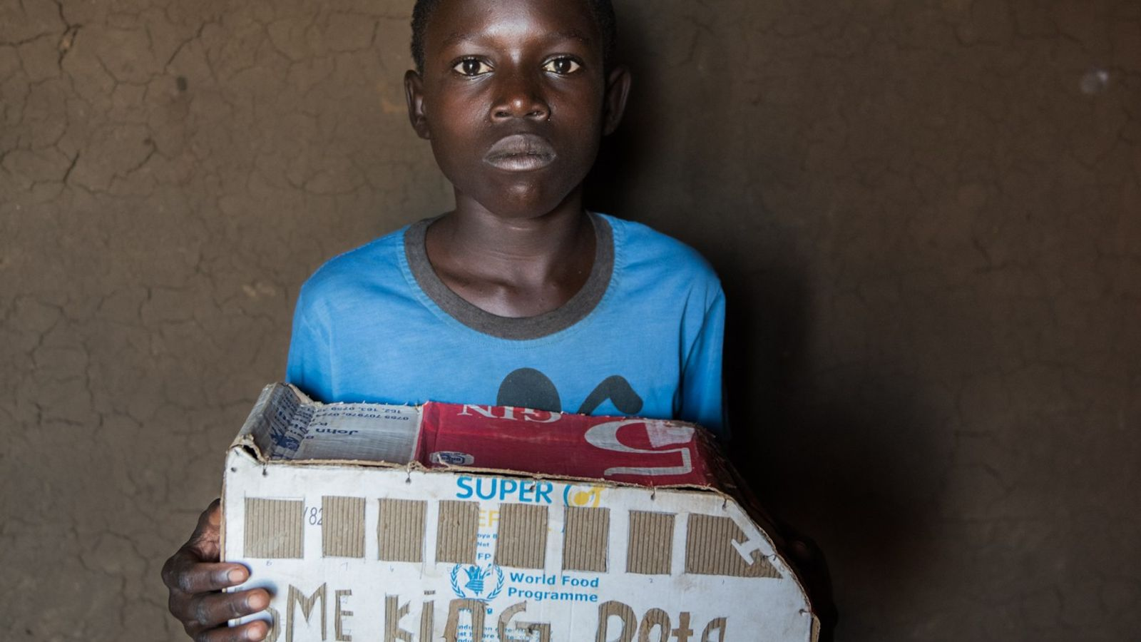 Isaac Lemi, a 13-year-old refugee from South Sudan living in Uganda, holds a toy bus he ...