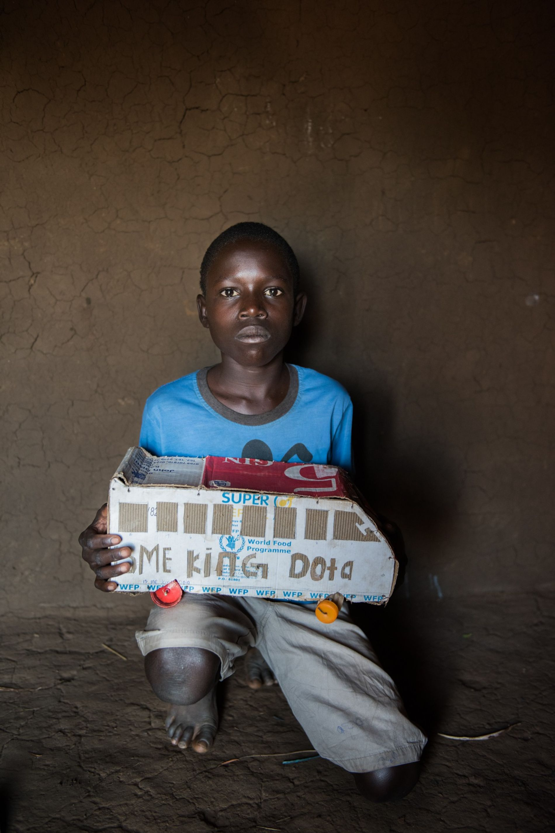 Isaac Lemi, a 13-year-old refugee from South Sudan living in Uganda, holds a toy bus he made out of a box from the World Food Program. Toys are scarce in Bidibidi, so children entertain themselves with handmade creations.