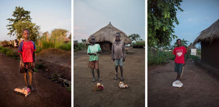 Dragging handmade cardboard trucks and cars, Peter Mandela (left), Wane Samuel and Cosmas Amule (centre), and ...