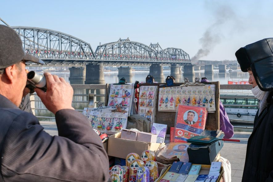 A man examines wares for sale at a tourist kiosk in Dandong near the China–North Korea ...
