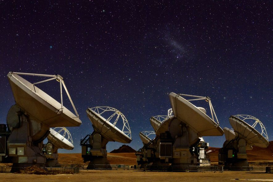 The night sky glimmers over the 66 radio antennas of the Atacama Large Millimetre/sub-millimeter Array (ALMA), ...
