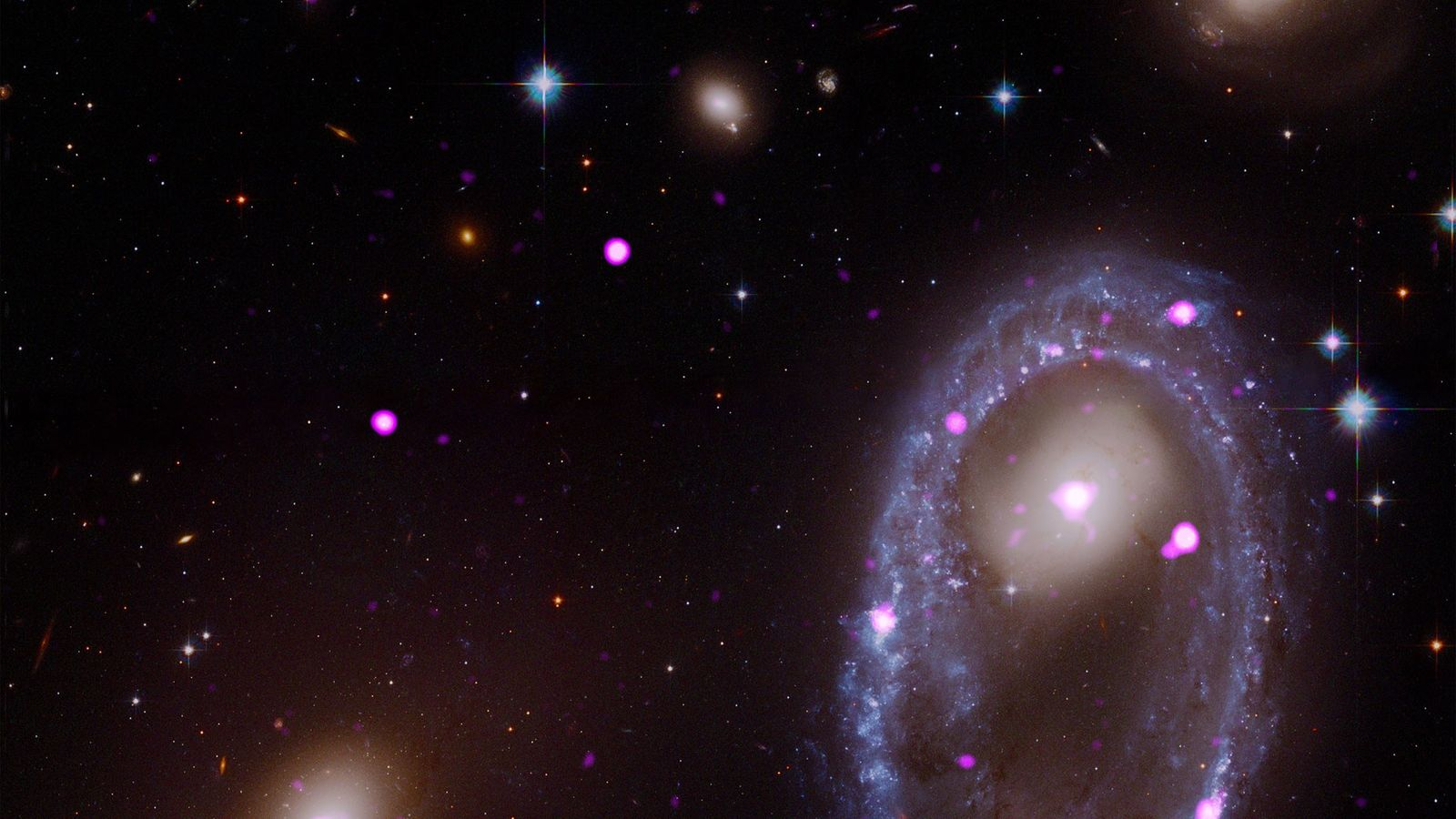 A composite image from the Hubble and Chandra space telescopes shows the ring galaxy known as ...