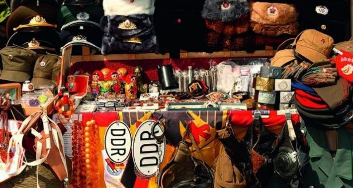 Tourist souvenirs, old DDR symbols and Soviet Russian uniforms for sale at stall next to Checkpoint ...