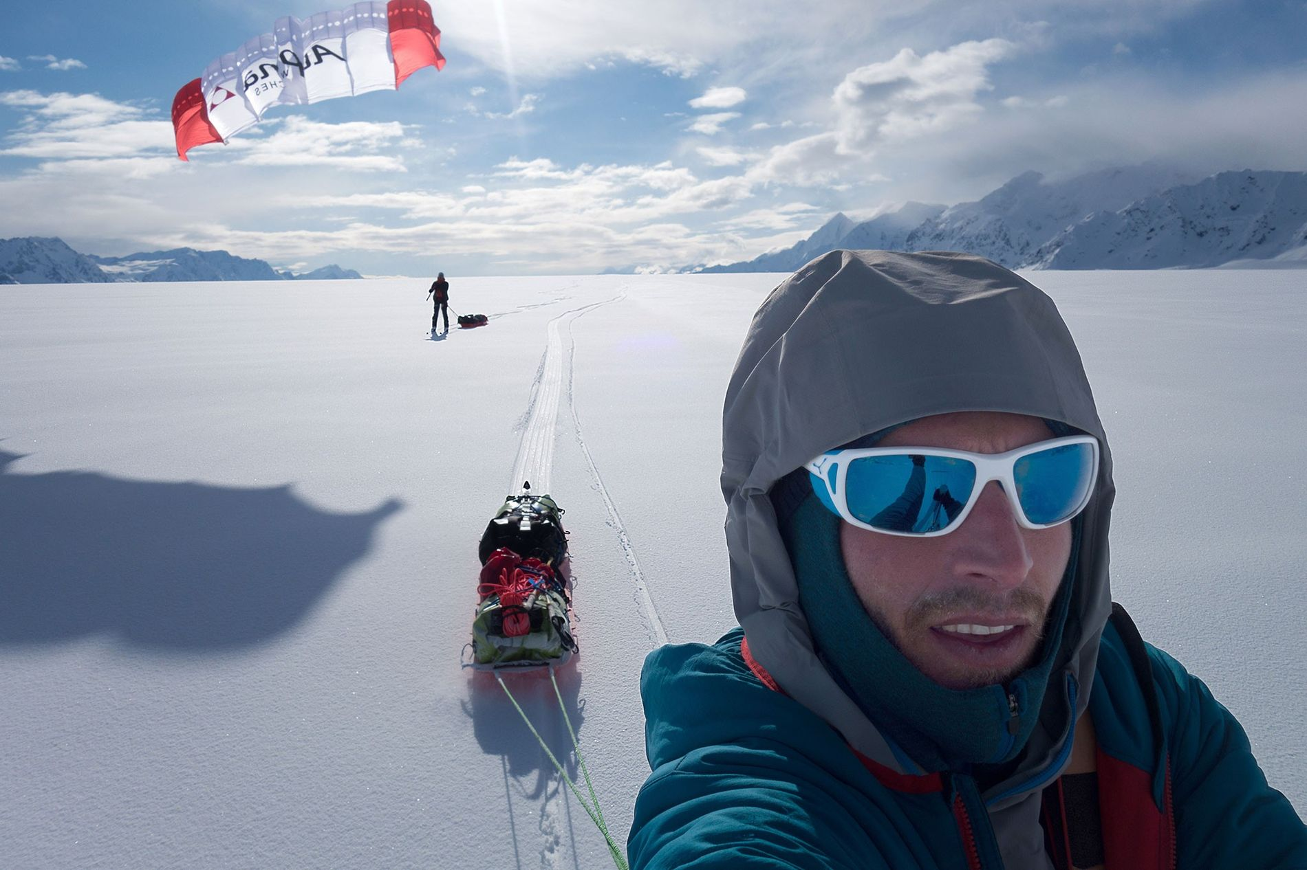 With the wind at their backs, the pair use ski-sails to pull themselves and their sleds along a portion of smooth terrain.
