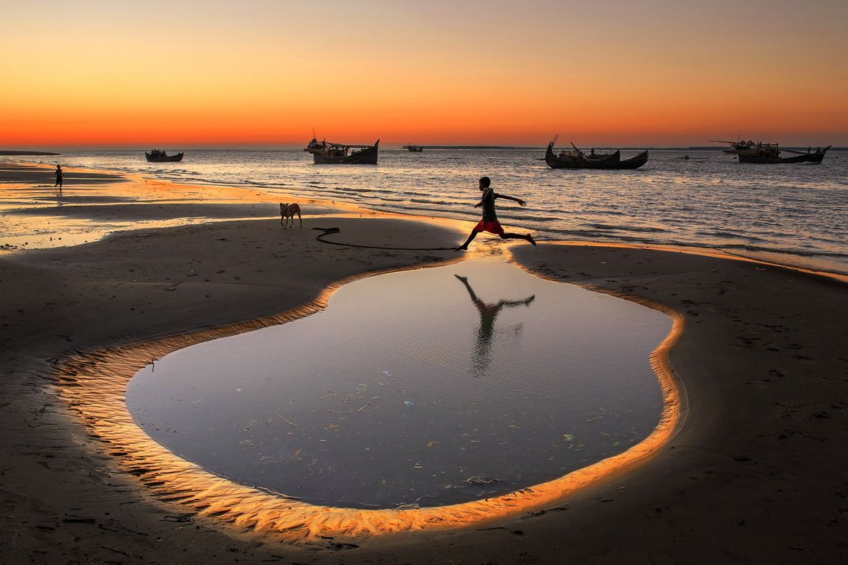 A boy crossing the little pond beside sea beach at Cox's Bazar Dry fishing village, Bangladesh. ...