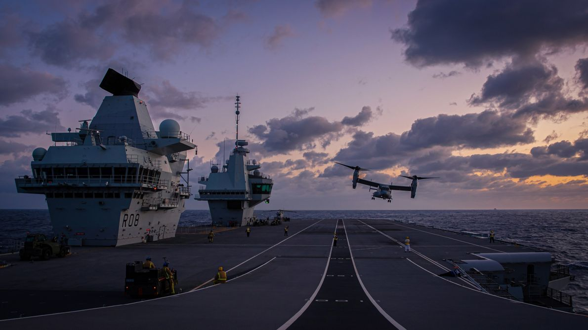 A US Navy Osprey aircraft lands on the deck of HMS Queen Elizabeth during night flight ...