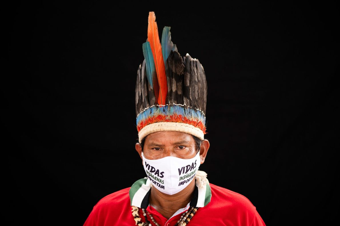 A leader of the Miranha tribe wears a traditional headdress and a face mask that reads ...