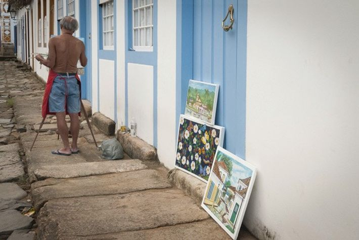 Tattooed fisherman painting the streets of Paraty.