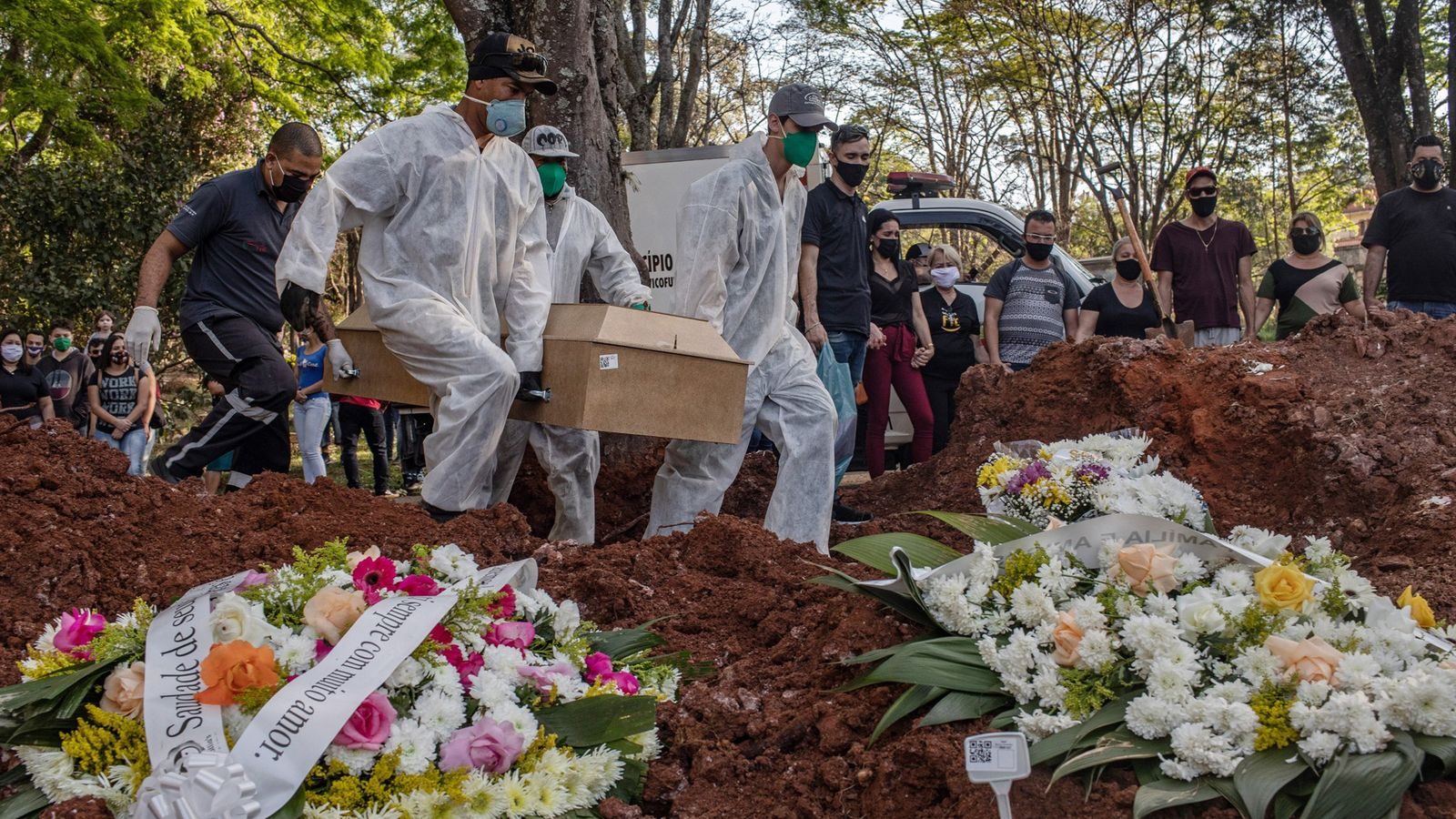 Gravediggers bury someone who died from th​e coronavirus at Vila Formosa​ Cemetery in São Paulo, Brazil, ...