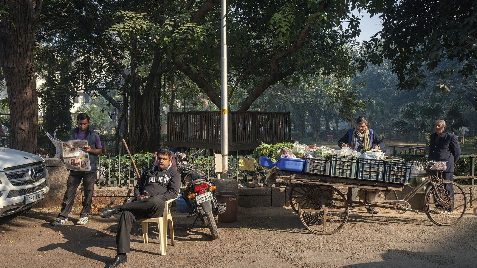 The Chandra's vegetable vendor checks his stock, while a driver reads the paper and a guard ...