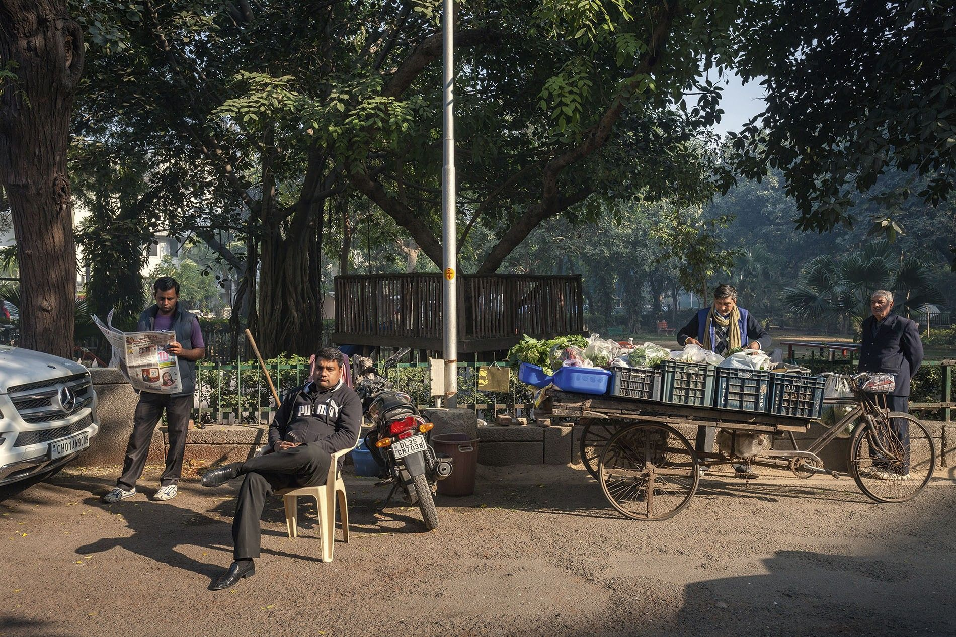 The Chandra's vegetable vendor checks his stock, while a driver reads the paper and a guard looks on.