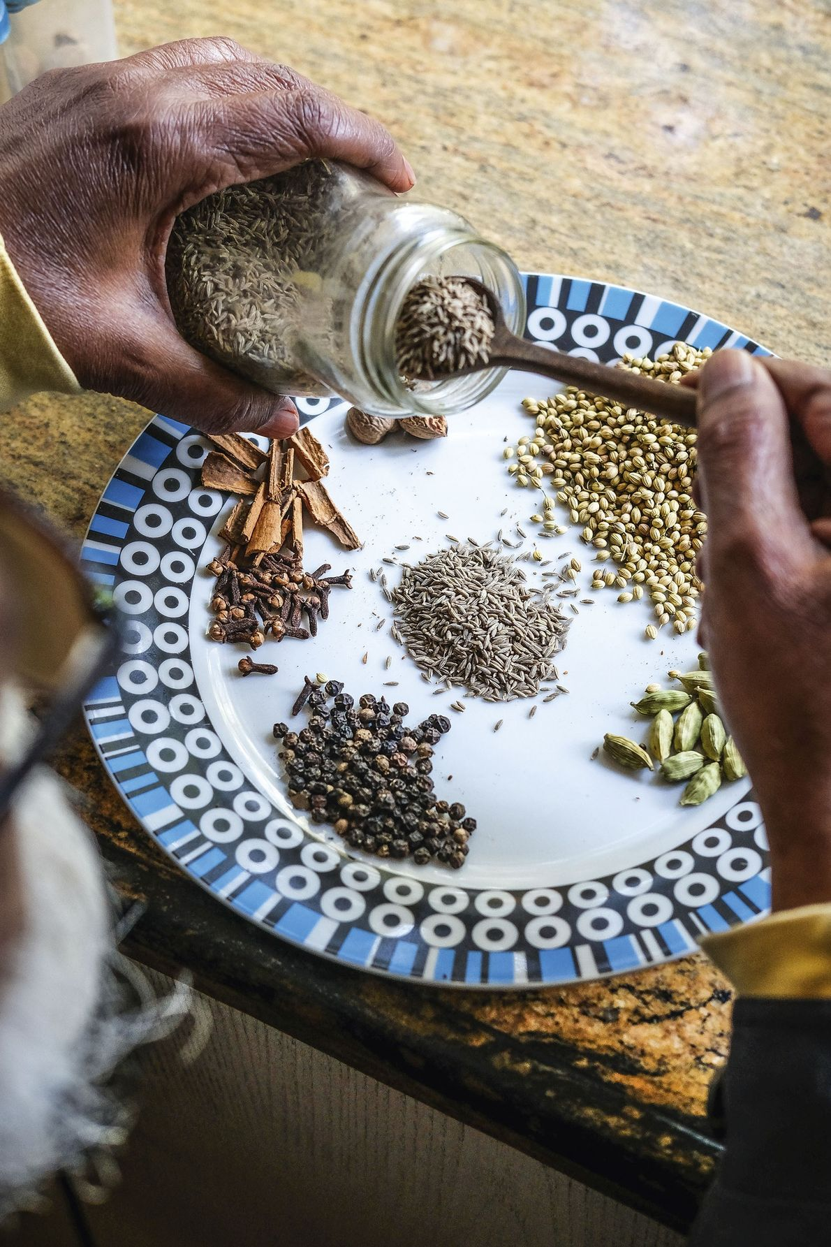 Anil Chandra measures out cumin seeds.