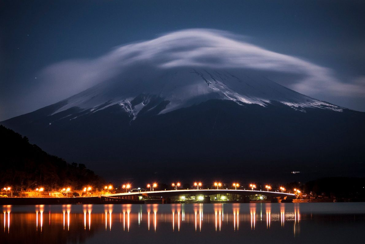 Mount Fuji glows in moonlight while Lake Kawaguchi is illuminated by highway lights around midnight.