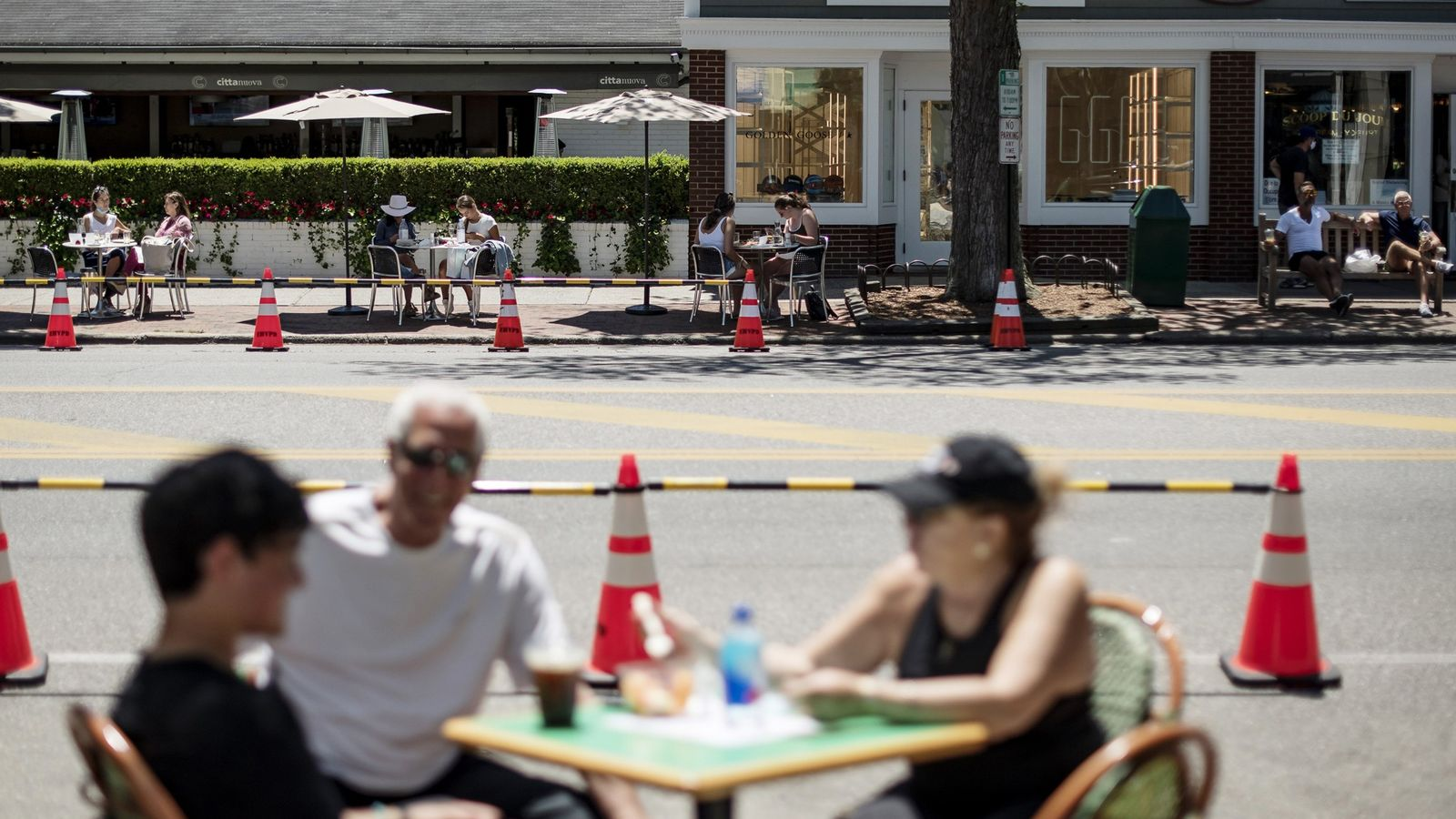 Diners sit at restaurant tables set up outdoors on both sides of Newton Lane in East ...