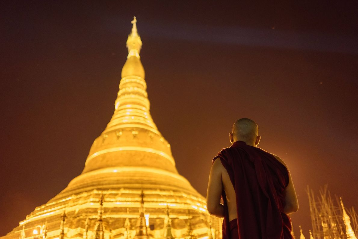 A buddhist monk contemplates the golden majesty of myanmar's most famous buddhist monument, the schwedagon pagoda.
