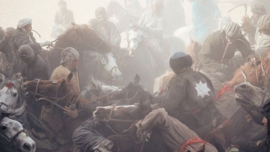 Horseback riders, or chapandazan, battle for control of a goat carcass during a buzkashi match in ...