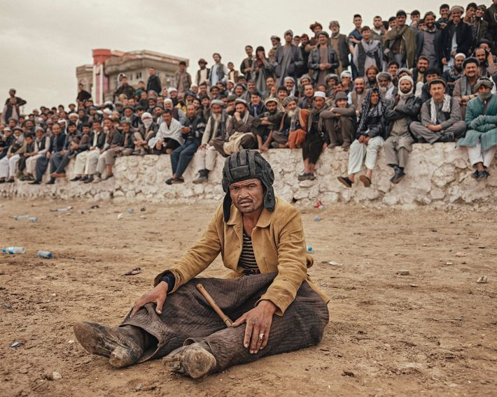 A chapandaz sits dazed on the ground after falling from his horse during a match in ...