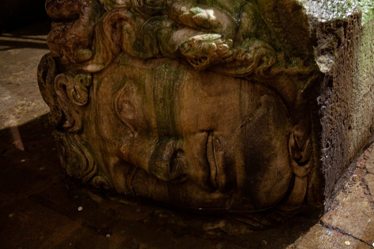 The ancient carved head of a medusa, set on its side, provides support for a column ...